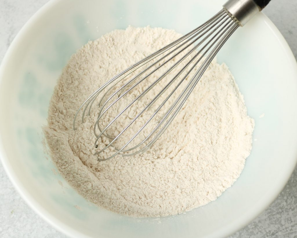 Dry ingredients mixed together in white bowl with a whisk.