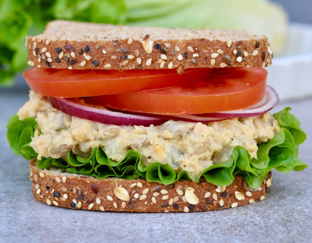 Close up, finished sandwich with vegan tuna salad, tomato, onion and lettuce with more lettuce and tomato blurred in the background.