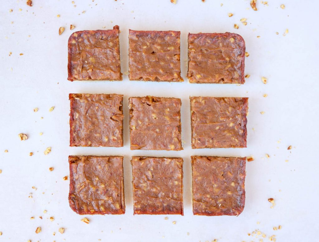 Finished pecan pie bars cut into 9 pieces with chopped pecans sprinkled around them.