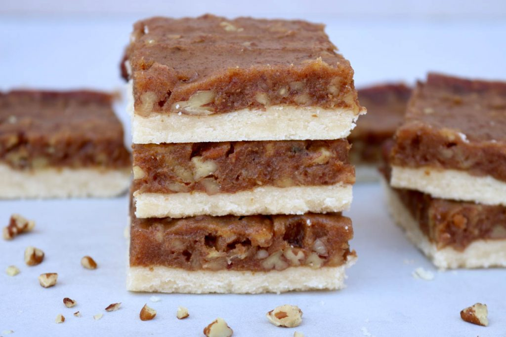 The finished bars stack on top of each other with other bars in the background and pecans scattered around them.