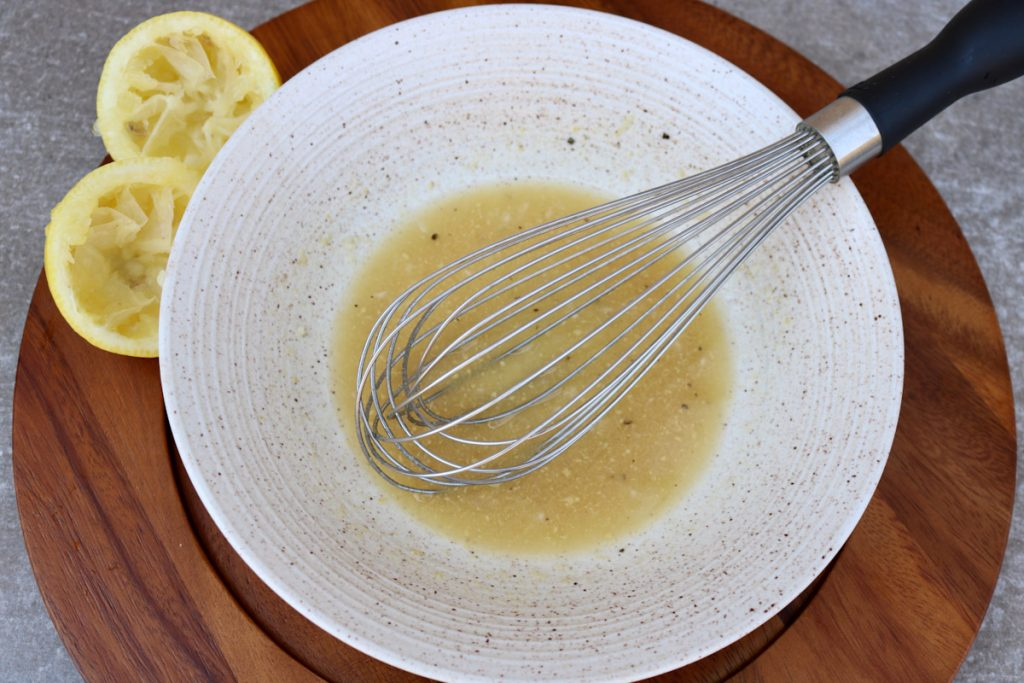 Bowl with a whisk and arugula salad dressing ingredients.