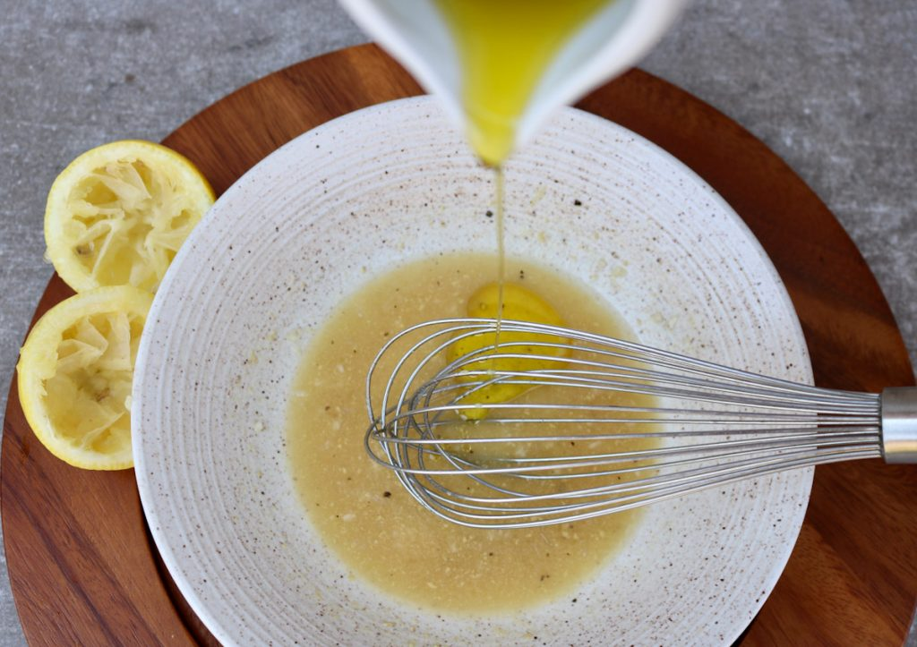 Bowl whisking dressing as olive oil is drizzled into dressing.