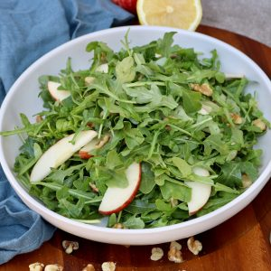 Finished apple arugula salad on a wooden board with a kitchen towel, lemon and walnuts in the background.