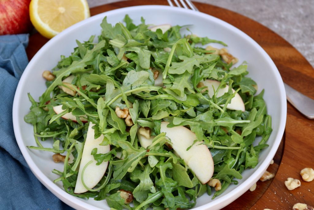 Finished arugula salad on a wooden board with a kitchen towel, lemon and walnuts in the background.