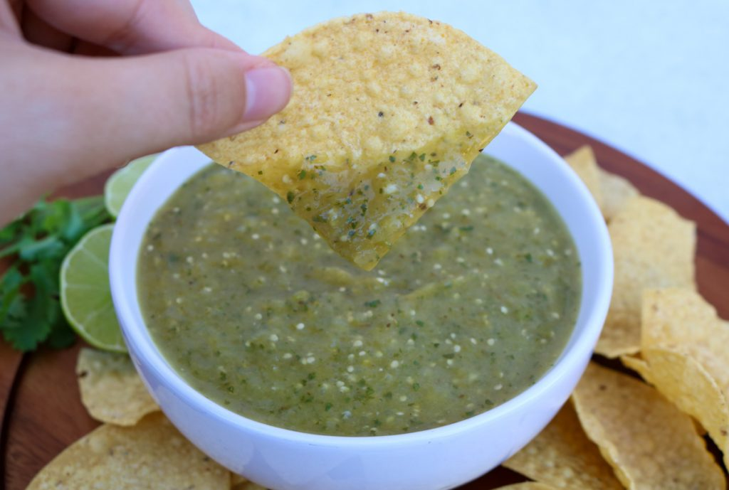Tortilla chip dipped in roasted tomatillo salsa with a white bowl of salsa, chips, lime and cilantro in the background.
