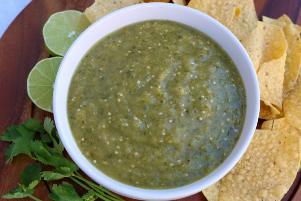 White bowl filled with roasted tomatillo salsa with chips, lime and cilantro around the bowl.