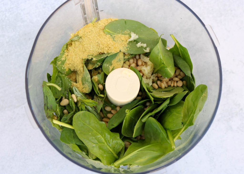 Basil, spinach, nutritional yeast, pine nuts, garlic and lemon juice in food processor.