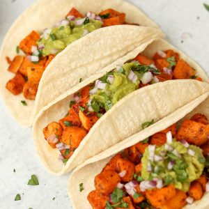 Close up, sweet potato tacos topped with guacamole, red onions and cilantro.