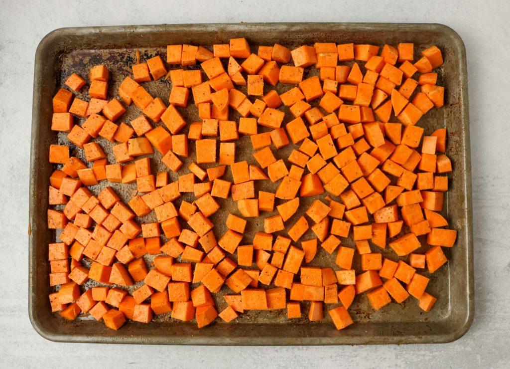 Seasoned sweet potatoes on a baking tray.