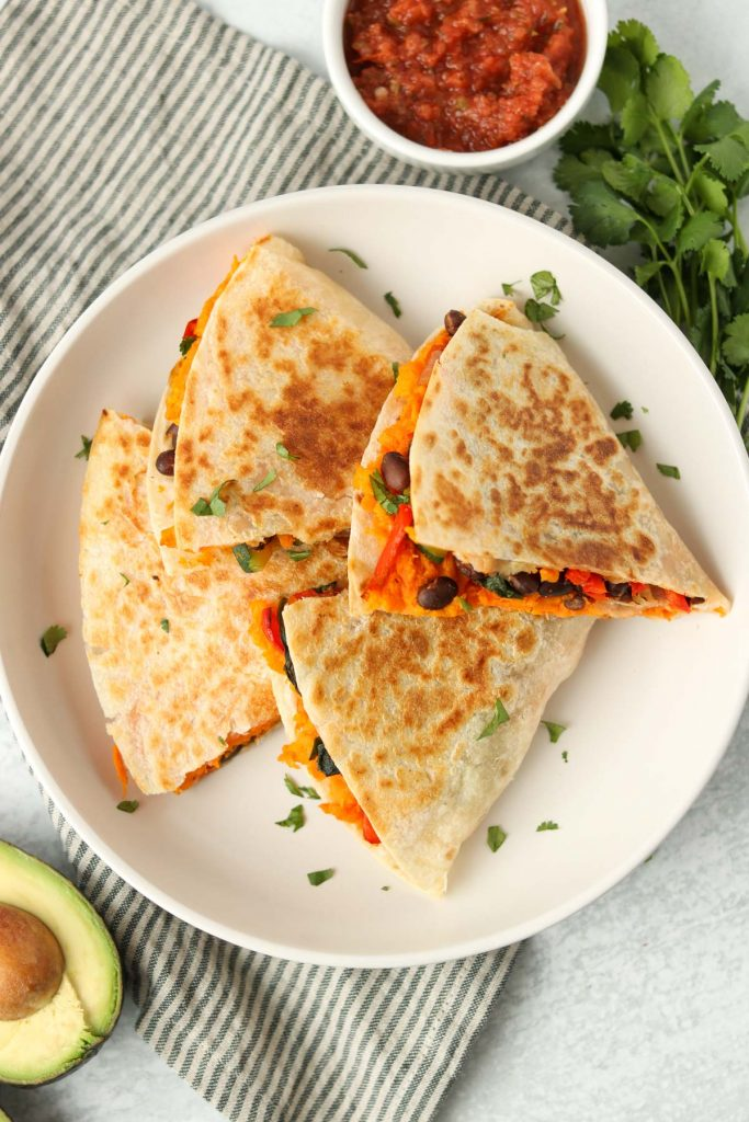 Overhead, quesadilla cut into sliced on a white plate with cilantro, avocado and salsa.