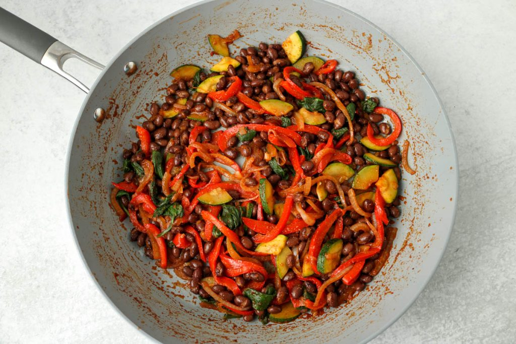 Cooked veggies and beans in pan.
