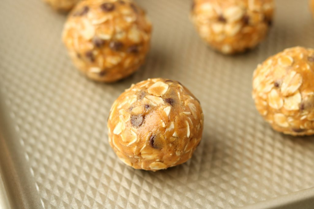 Close up, one finished peanut butter ball with more blurred in background.