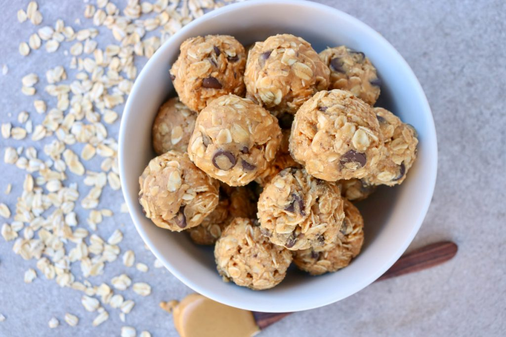 Overhead, finished balls in white bowl with oats scattered around and a wooden spoon with peanut butter.