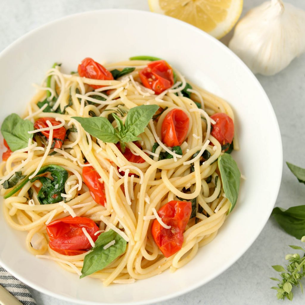 Finished pasta in a white bowl with fresh basil on top.