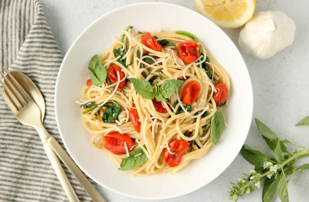 Finished pasta in a bowl topped with fresh basil.
