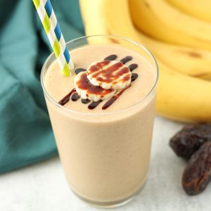 Close up, finished smoothie in a glass with banana slices on top and two straws.