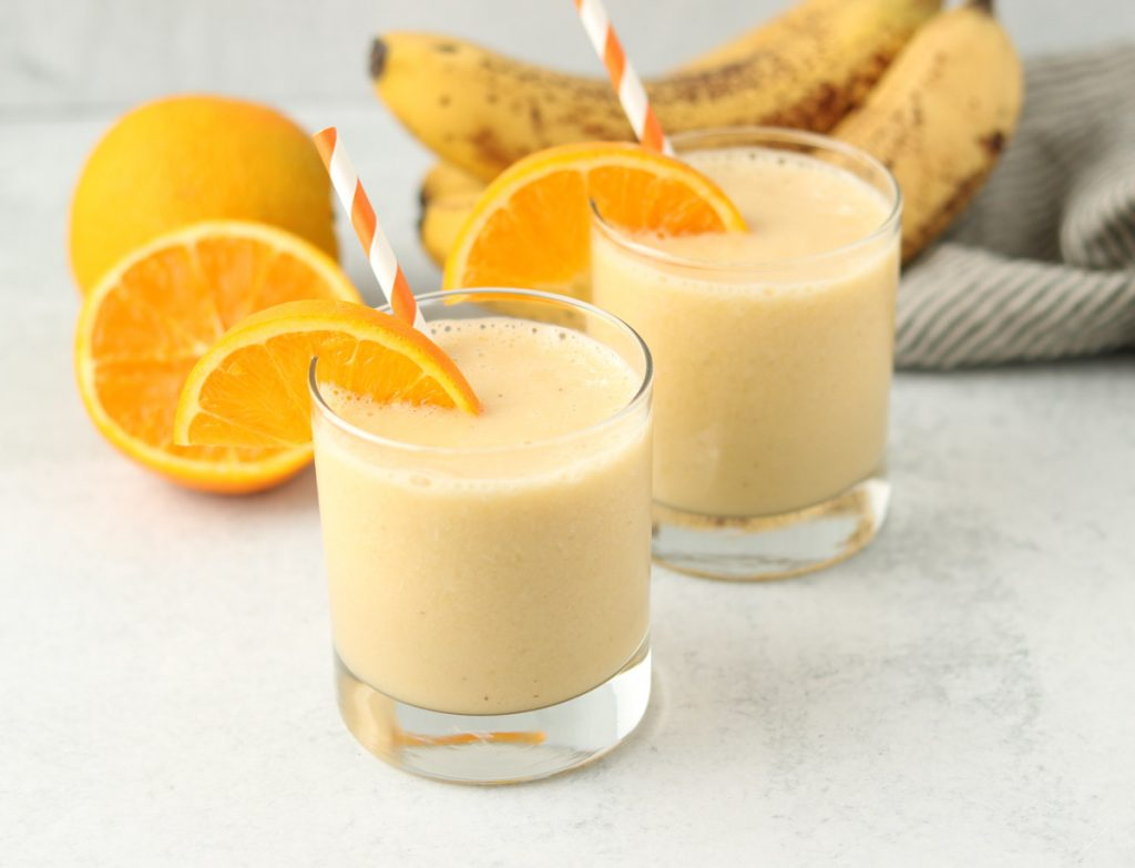 Two finished smoothies with a slice of orange and an orange stripped straw.