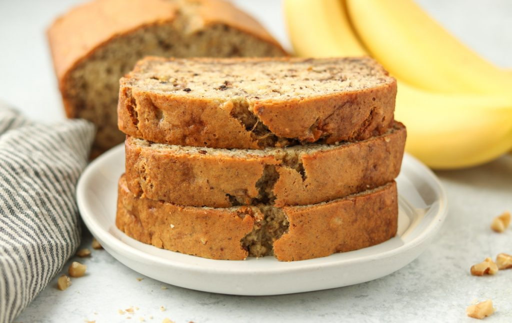 Three slices banana bread stacked on top of one another on a plate.