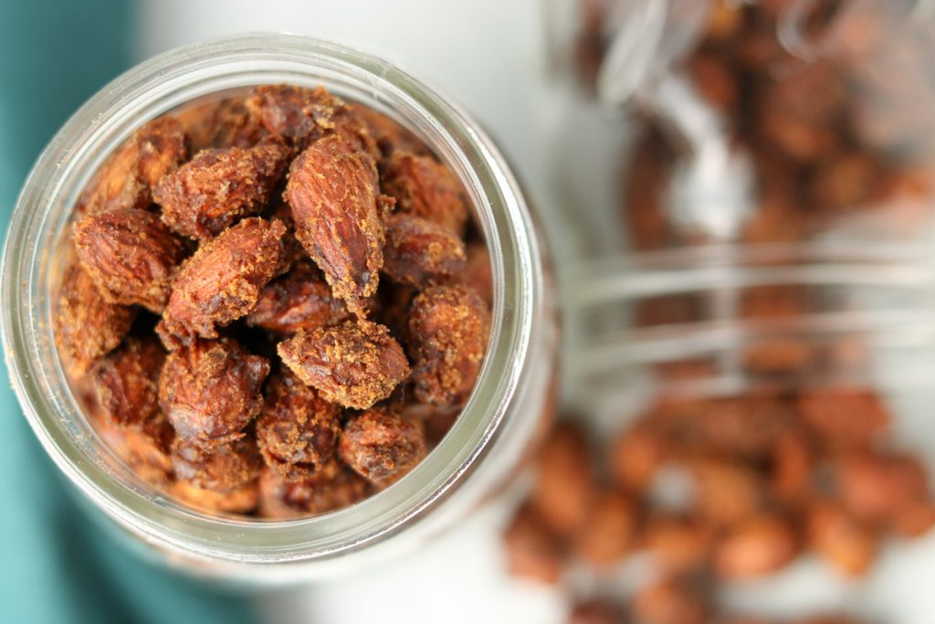 Over head, finished almonds in a mason jar with another jar spilled over.