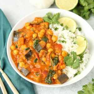 Curry in a bowl with rice, cilantro and lime.