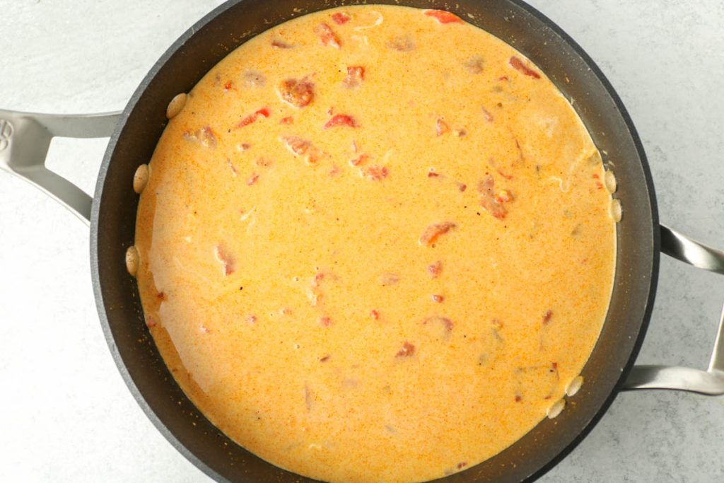 Coconut milk and diced tomatoes added and incorporated together.