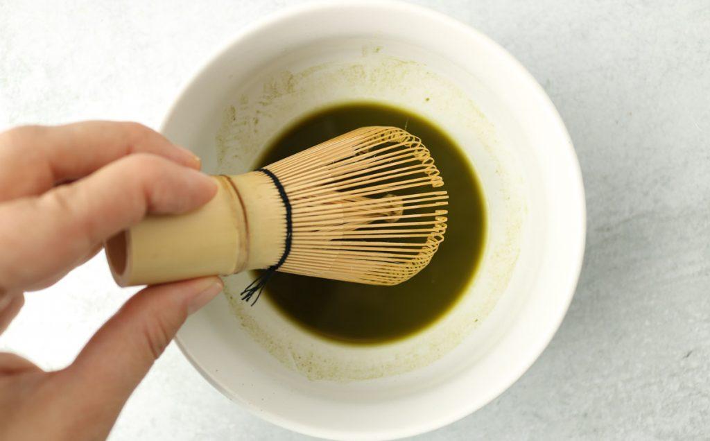 Matcha powder in a large mug mixed with hot water.