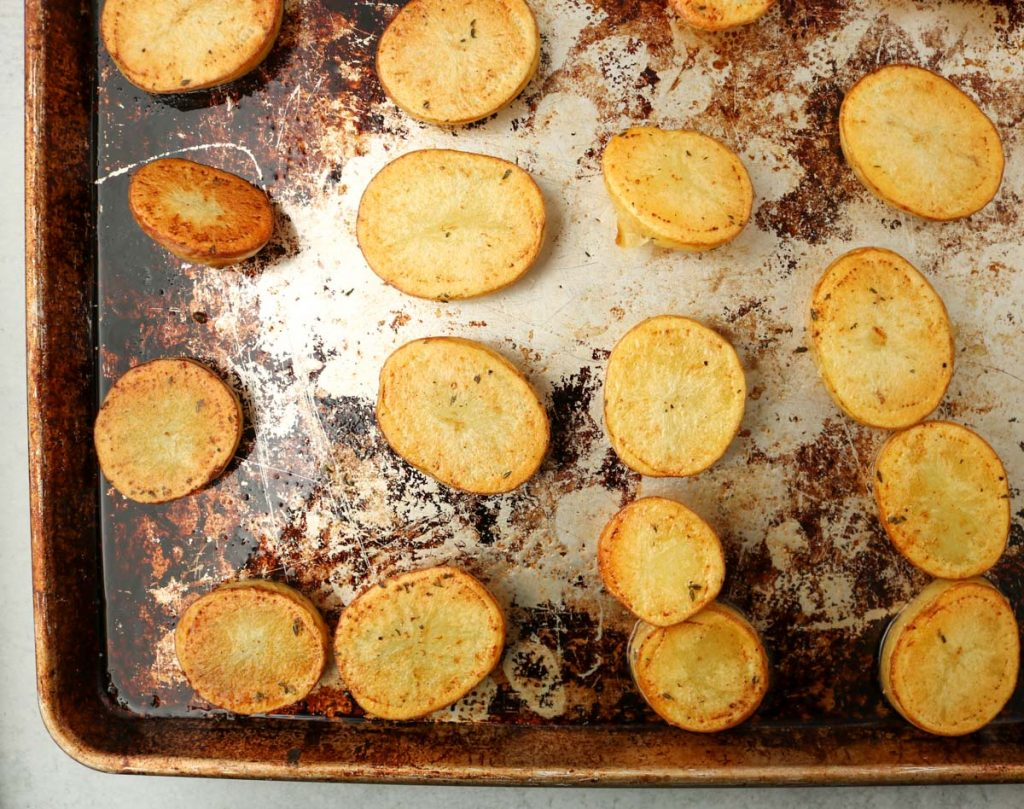 Potatoes on sheet pan with one side golden brown.