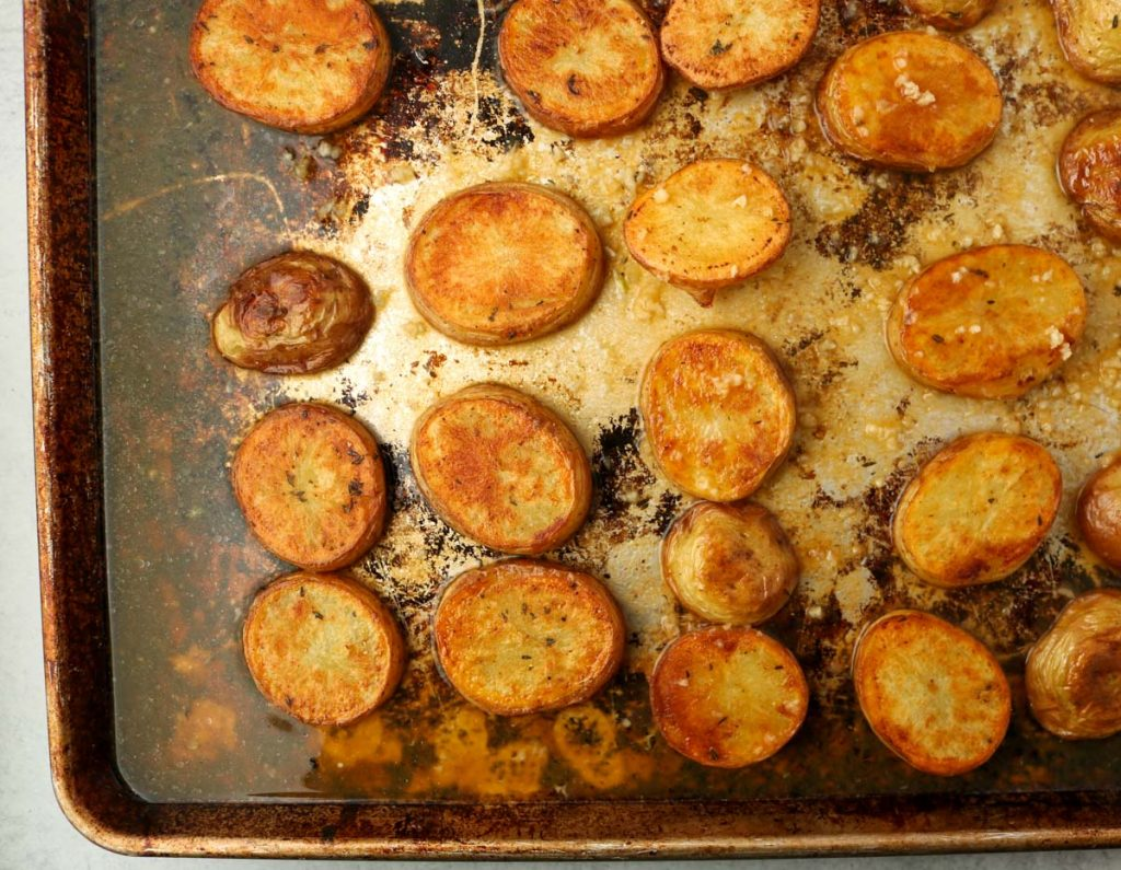 Potatoes on sheet pan with vegetable broth and garlic added to pan.